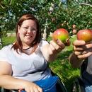 Deux personnes en fauteuil roulant présentant des pommes dans leur main