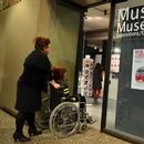 Personne en fauteuil roulant devant l'entrée du musée